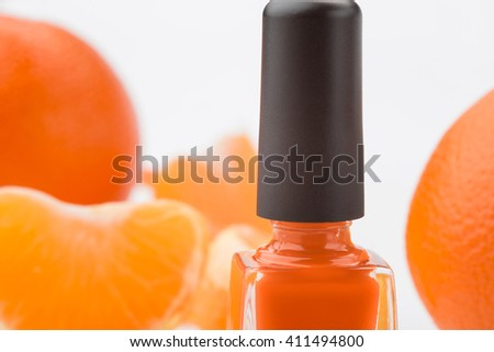 Nail polish in macro. Beautiful pleasant orange color for simple manicure. Juicy citruses and its segments in the background. Bright picture for wallpaper. - stock photo