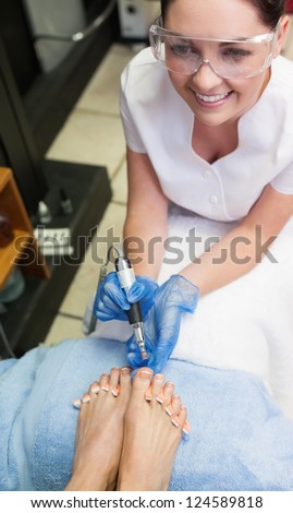 Nail technician removing callus at feet in nail salon - stock photo