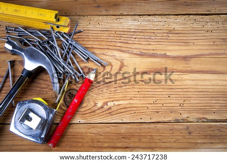 Nails, hammer, roulette, pencil and folding ruler on wooden background - stock photo