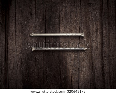 Nails lying on wooden  surface. Conceptual image of home improvement, DIY and carpentry.