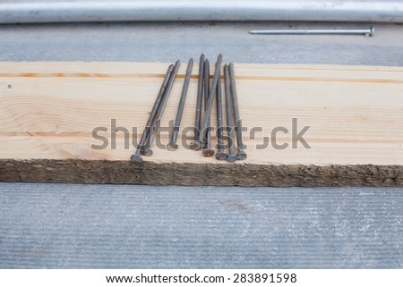 nails on wooden plank - stock photo