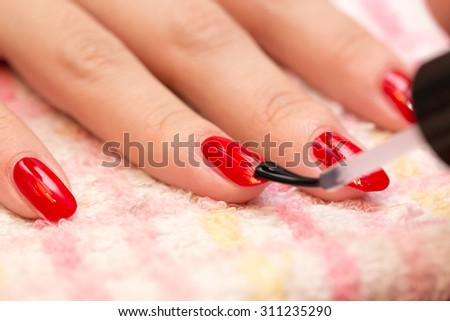 nails painted red nail polish in a beauty salon - stock photo
