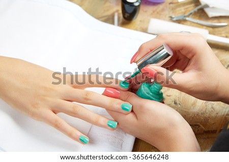 Nails painting with brush in Nail Salon woman hands - stock photo