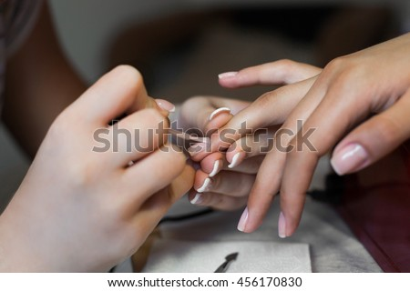 Nails saloon woman applying nail polish