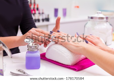 Nails saloon woman nail polish remove with tissue for new manicure - stock photo