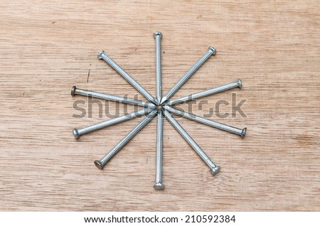 nails star shape on wood background - stock photo