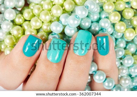 Nails with manicure covered with nail polish on colored pearls background - stock photo