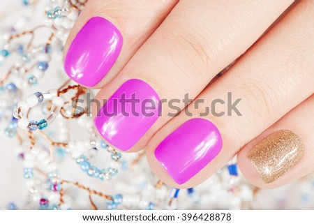 Nails with manicure covered with pink and gold nail polish  - stock photo