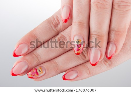 nails with teddy bear painting and hands isolated on white background