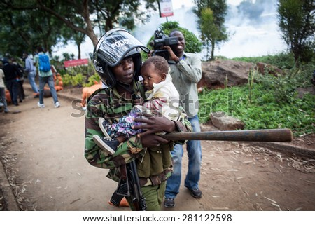Nairobi, Kenya - February 13, 2014: A Kenyan riot police officer carries a baby during a protest. - stock photo