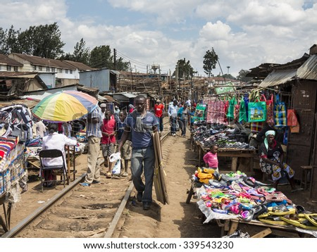 NAIROBI, KENYA-NOVEMBER 7, 2015: Unidentified people buy and sell in a large makeshift market along the railroad in Kibera, the largest urban slum in Africa. - stock photo
