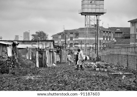 NAIROBI, KENYA OCT. 13: Unidentified people walk in mud through the Nairobi slum Oct. 13 2011 in Nairobi, Kenya. Kibera is the largest slum in Nairobi, and the second largest urban slum in Africa - stock photo