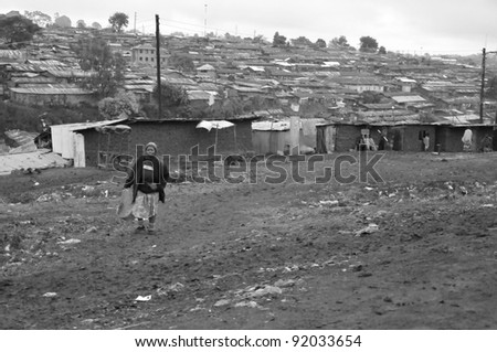 NAIROBI, KENYA OCT. 13: Unidentified woman walks in mud through the Nairobi slum Oct. 13, 2011 in Nairobi, Kenya. Kibera is the largest slum in Nairobi, and the second largest urban slum in Africa - stock photo