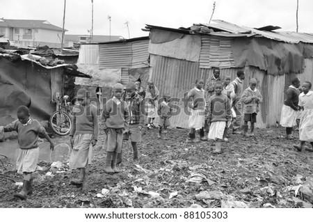 NAIROBI, KENYA - OCTOBER 13: Unidentified children walk in mud for to go school on 13 October 2011 in Nairobi, Kenya. Kibera is the largest slum in Nairobi, and the second largest urban slum in Africa - stock photo