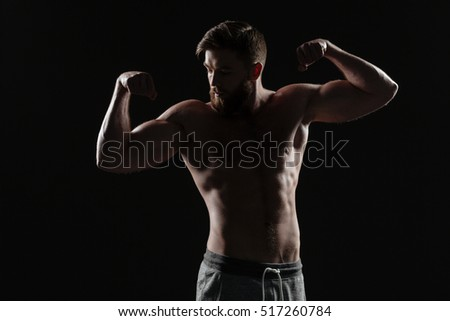 Naked athletic man demonstrates biceps. isolated dark background
