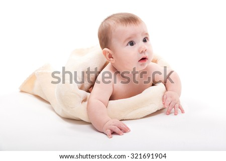 naked baby lies on his back and looks at the camera, picture with depth of field