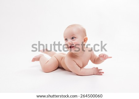 naked baby on a white background smiling and looking at the camera, shot with depth of field - stock photo