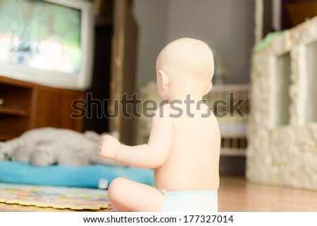 naked baby watching TV sitting on the floor��� in a diaper - stock photo