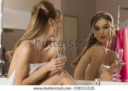 naked beautiful woman covering her breast with white towel and preparing for new year party in front of mirror, drinking champagne  - stock photo