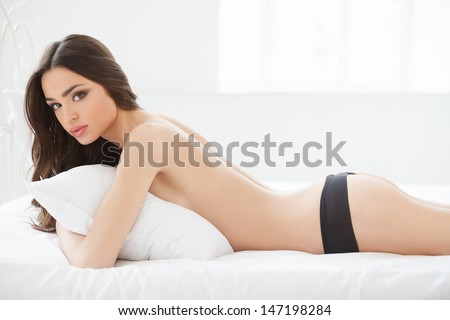 Naked beauty. Beautiful young women in lingerie lying on her front and looking at camera - stock photo