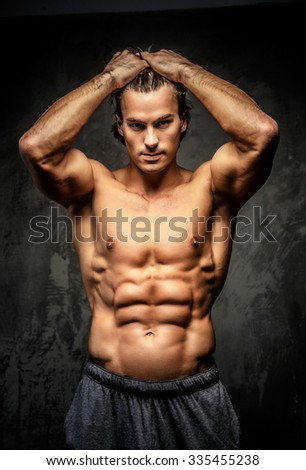 Naked bodybuilder holding his head. - stock photo