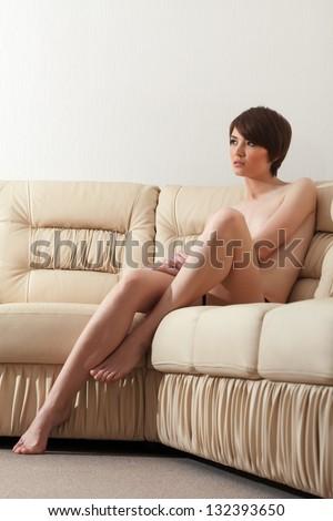 Naked brunette posing on beige leather sofa - stock photo