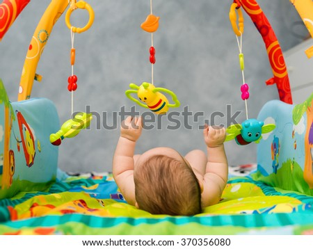 naked child playing lying on Developing rug - stock photo