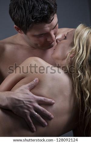 Naked couple kissing over grey background - stock photo