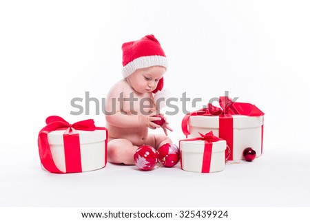 Naked cute baby sitting on a white background in a New Year's cap among packaged gifts and Christmas balls, picture with depth of field - stock photo