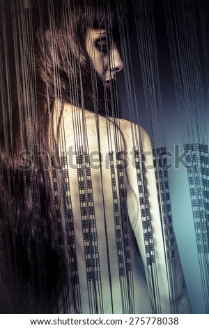 naked girl behind curtains of black threads