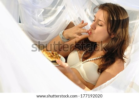 Naked girl having breakfast in the tissues - stock photo