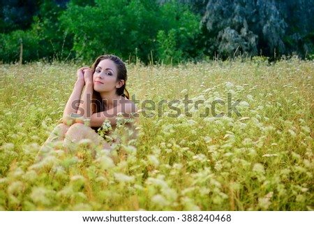 Naked girl in a field of wildflowers - stock photo