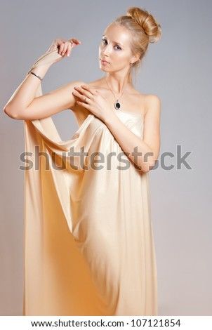 naked girl in the gold drapery - stock photo