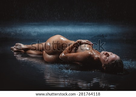 naked girl on a beach in the rain - stock photo