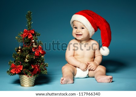 naked little boy in diapers with hat of Santa Claus