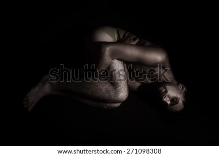 Naked lonely young man lying on the floor - stock photo