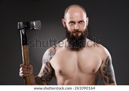 Naked lumberjack. Topless bearded man holding old axe on gray background - stock photo