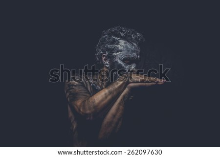 naked man covered with paint and mud skin - stock photo