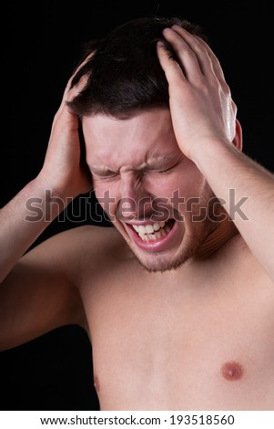 Naked man suffering from headache on isolated background