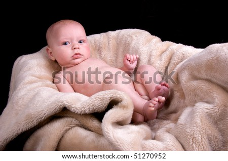 naked 3 month old baby lying on a fluffy blanket - stock photo