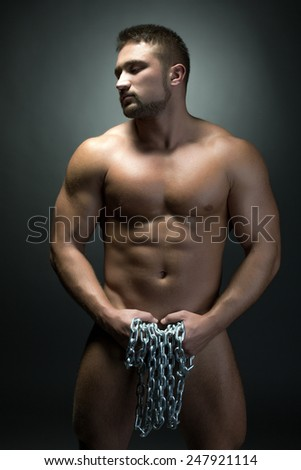 Naked muscular man posing with chain - stock photo