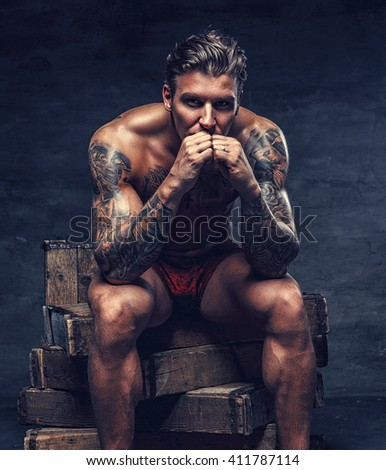 Naked muscular tattooed guy sitting on wooden boxes.