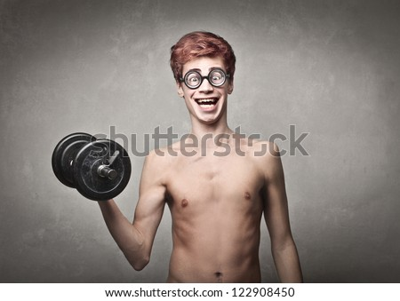 Naked nerd guy raising a dumbbell