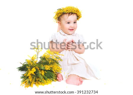Naked newborn baby with a wreath of mimosa flowers - stock photo