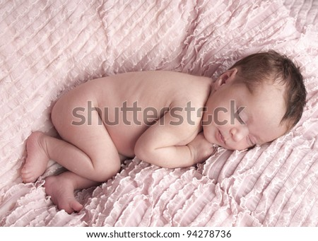 Naked newborn girl one week old asleep in the fetal position on a ruffled pink blanket - stock photo