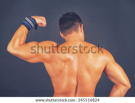 Naked sexy bobybuilder stand back - stock photo