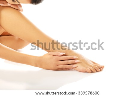 Naked slim woman sitting curled up touching her leg - stock photo