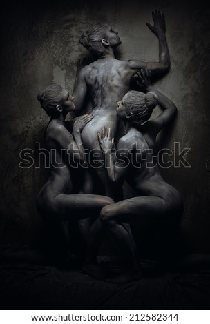 Naked sportive women painted in grey color posing over grey wall  - stock photo