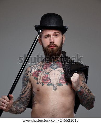 Naked tattooed male in hat with holding walking stick in his hand - stock photo