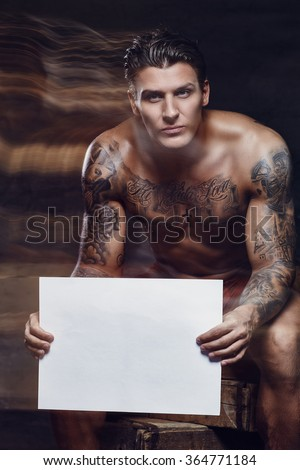Naked tattooed muscular man posing in studio. Your text here.